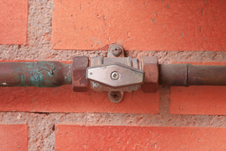 Gas pipes and valve in the open position against a red brick wall