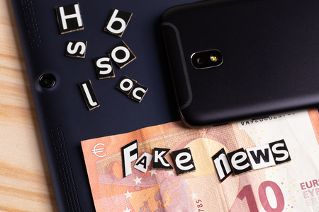 The concept of news mobility: a tablet, a touchscreen phone on one table and a cut from the text with letters and money to pay for the release of false information Imagens