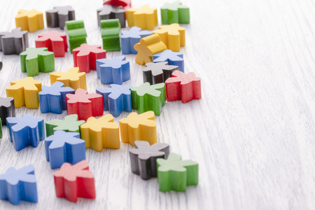 Bunte Holzfiguren in Form von Sternen. Teile des Brettspiels. Führungskompetenz. Die Entwicklung der Logik. Nummer eins, Gewinner und Verlierer. Hinterer und vorderer Hintergrund in Unschärfe.