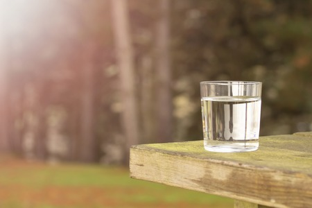 Clear water in a transparent glass on an old wooden table against the background of coniferous forest. Healthy food and ecologically pure natural water from a spring Imagens