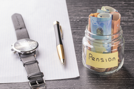 Glass jar with coins and euro banknotes with the words PENSION. Wrist watch, pen and blank paper. Concept of financial savings for wealthy old age