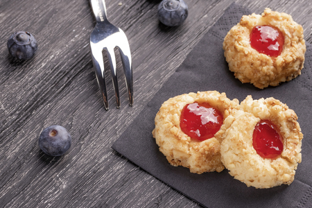 Cookies made from hazelnut shortcake with strawberry jam inside on a black napkin with blueberries and a patterned dessert fork on a dark background nearby.