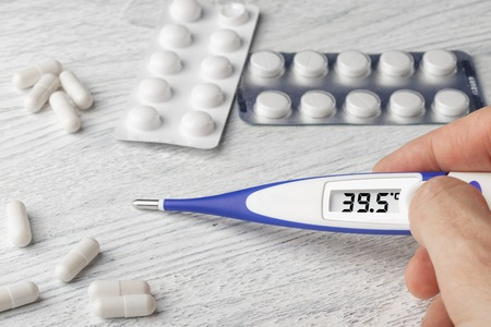 White-blue thermometer with a high temperature of 39.5 degrees Celsius in hand with pills and medical capsules on a wooden background Stockfoto