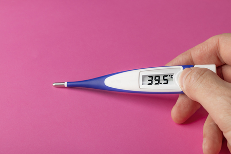 White-blue thermometer with a high temperature of 39.5 degrees Celsius in hand on a pink background