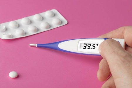 White-blue thermometer with a high temperature of 39.5 degrees Celsius in hand with medical pills on a pink background Stockfoto