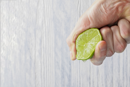 The hand of a man squeezes the juice from a slice of lime half. Juicy drop hanging down. Light wooden background. Foto de archivo
