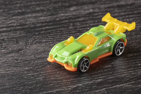Yellow and green car toy on a dark wooden background