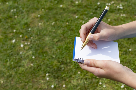 Boy's hand with a yellow-black pencil over an open notepad on a background of green grass and white flowers in the park. Clean white sheet. Going to write or draw a picture.