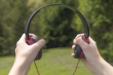 Red-black headphones in the hands against the background of coniferous trees on the green grass and mountains in the distance. Relaxation concept to the sounds of nature Archivio Fotografico