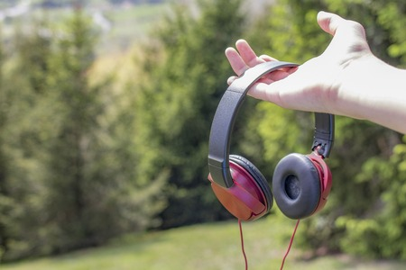 Red-black headphones in hand on the background of coniferous trees on the green grass and mountains in the distance. Relaxation concept to the sounds of nature