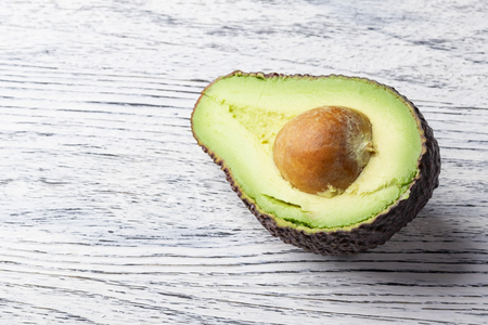 Half a juicy ripe avocado with a round bone and reddish peel on a white wooden table background