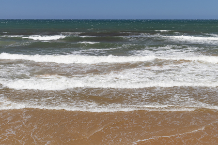 Stunning view of the ocean calm surf with quiet waves reaching the sandy shore and clear turquoise water and clear skies. Tourist's dream