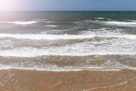 Ocean surf with sandy beach and turquoise water on a sunny summer day. Traveler's sleep