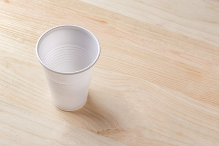 White plastic Cup stands on a wooden table of natural color. the concept of abandonment of plastic utensils