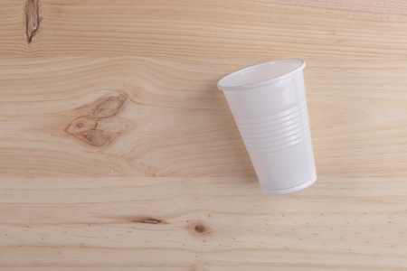 White plastic Cup is on a wooden table of natural color. the concept of the end of the party and the rejection of plastic utensils