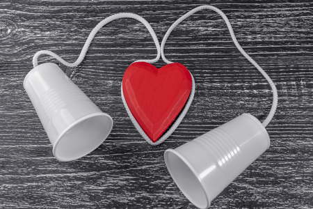 The phone is made of white plastic cups and a white rope laid around a red wooden heart on a black table. The concept of emotional contact between lovers