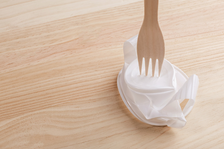 White plastic cup crumpled with a wooden eco fork on the wood table. The concept of excellence eco products over plastic
