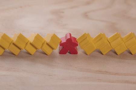 Wooden figures in the form of people or in the form of stars. Several yellow figures leaned on one red. The concept of a large psychological burden on the boss and employee