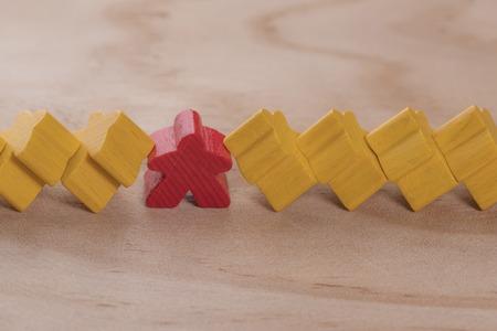 Figuras de madera en forma de personas o en forma de estrellas. Varias figuras amarillas se apoyaron en una roja. El concepto de una gran carga psicológica para el jefe y el empleado.