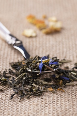 Green tea with orange peel and herbs with blue flowers. On a sackcloth with a dessert spoon