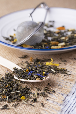 Green tea with orange peel and herbs with blue flowers. On a sackcloth with a dessert wooden spoon with strainer