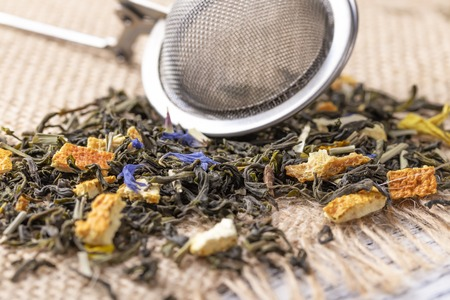 Green tea with orange peel and herbs with blue flowers. On a sackcloth with strainer