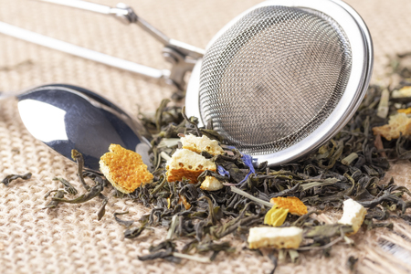 Green tea with orange peel and herbs with blue flowers. On a sackcloth with a dessert spoon with strainer Imagens