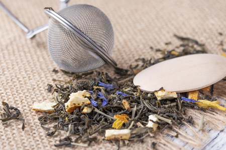 Green tea with orange peel and herbs with blue flowers. On a sackcloth with a wooden dessert spoon with strainer