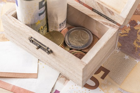 Wooden old chest with euro coins and banknotes. The concept of financial savings for old age