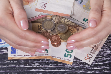 Female hands closes off a pile of euro banknotes and coins on a black wooden table. The concept of financial stability and reliability of bank deposits