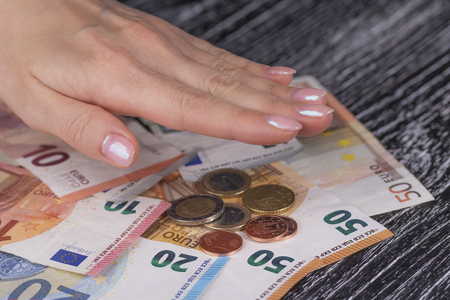 Womans hand with pink nails covered a pile of euro banknotes and coins on a black old table. The concept of annual budget and reliable bank deposits