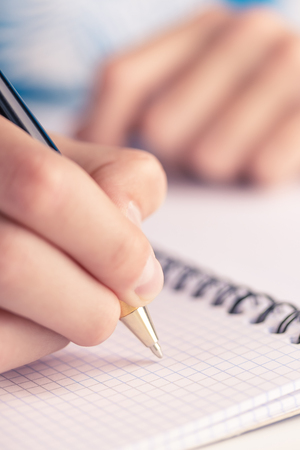 Teen writes black yellow pen in a checkered notebook. Homework and daily plan