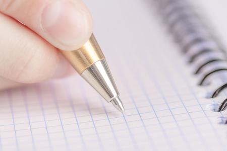 Teen writes black yellow pen in a checkered notebook. Spiral bound