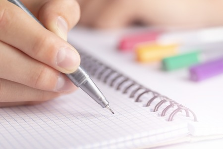 Teen writes black yellow pen in a checkered notebook. With colored markers Stock Photo