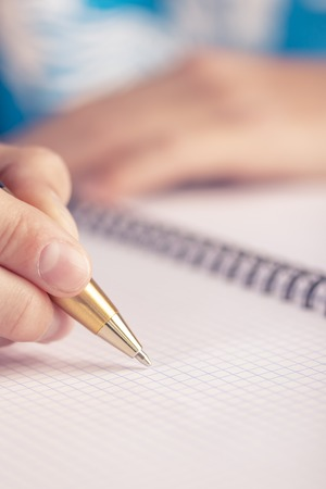 Teen writes black yellow pen in a checkered notebook. Exam at school Stock Photo