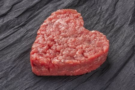Beautiful juicy meat cutlet on a contrasting black background. The concept of nutrition in sports