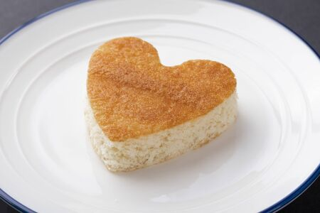 A heart-shaped cupcake on a white plate with a blue border. Lovers day and birthday celebration concept