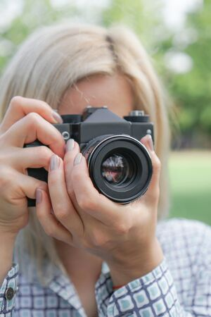 Blonde girl holds a camera and focuses in the forest. Against the background of green grass and trees. Image for the photographer business card.