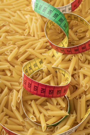 Multicolored centimeter in a pile of wheat pasta. The concept of body control and eating restrictions