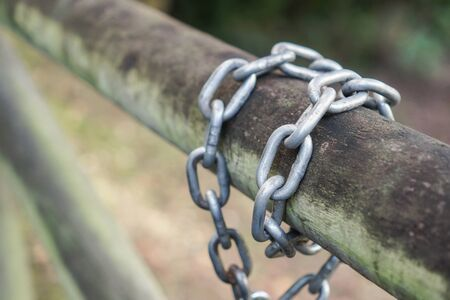A metal chain is wound around a log gate in a park. The concept of strength and reliability