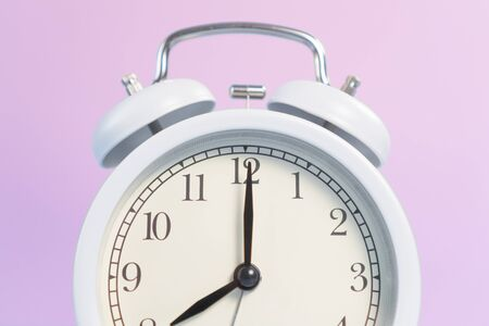 White analog classic alarm clock with black arrows on a pink creative background. The concept of transience of time