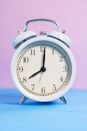 White analog classic alarm clock with black arrows on a pink and light blue creative background. Vertical view. The concept of transience of time