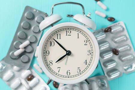 Bright alarm clock with black arrows in a pile of blister packs with medical tablets on a bright neon background. Idea of sleep control