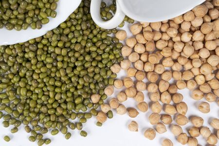 Turkish peas and Green mung bean are poured in handfuls of white cups on the table. View from above. Asian traditional food ingredients