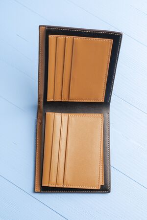 Empty open leather wallet on a wooden blue plank background. Vertical view. The concept of financial crisis after the coronavirus pandemic Stock fotó
