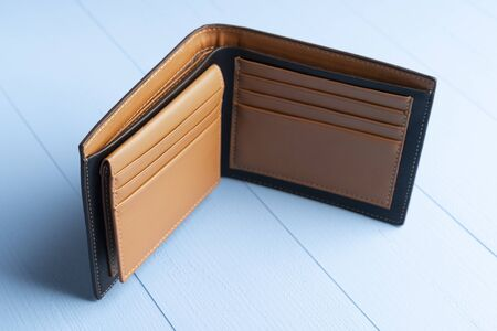 Empty open leather wallet on a wooden blue plank background. The concept of financial crisis after the coronavirus pandemic