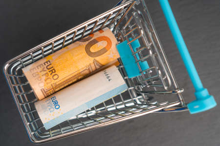 Shopping cart with euro banknotes on a dark background. Finance concept. View from above.
