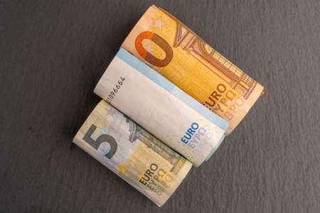 Euro banknotes rolled into a tube on a dark stone background. Financial crisis concept