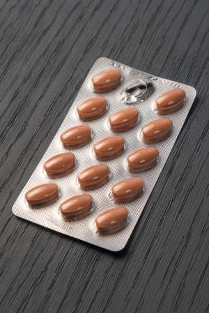 Brown pills in a silver blister pack on a dark wooden gray texture close up Standard-Bild
