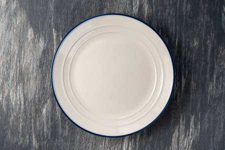 White plate with blue border on a beautiful gray wooden background. Empty kitchen utensils on art surface Standard-Bild